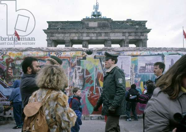 Fall of the Berlin Wall: a police officer in front of the Wall in West Berlin. Behind the Wall is the Brandenburg Gate. 11/1989.