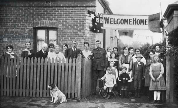 Group portrait of 540 Sapper Arthur Findon Dunbar MM, 2nd Australian Tunnelling Company (in uniform with his arm resting on gate) and his family members gathered outside their house at 45 Chief Street, Brompton, SA, July - August 1919 (b/w photo)