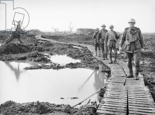 Four Australian soldiers walking along the duckboard track at Tokio, near Zonnebeke, in the Ypres sector, over a portion of the country captured by the Australians in the fighting of the Third Battle of Ypres, 22 October 1917 (b/w photo)