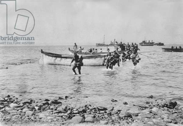 Australian soldiers wading through the water as they come ashore at Anzac Cove, Gallipoli on 25 April 1915 after being transported in landing boats from larger ships in the background, 25 April 1915 (b/w photo)