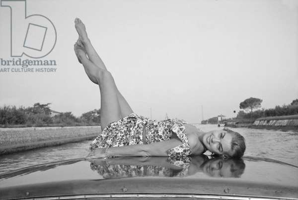Esther Williams sitting on a boat, Italy, 1957 (b/w photo)