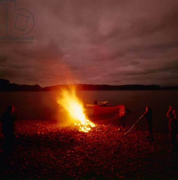 A bonfire by the lake lighting the night on 24th of June, the day of the summer solstice and the feast of Saint John, Finland, 1960s (b/w photo)