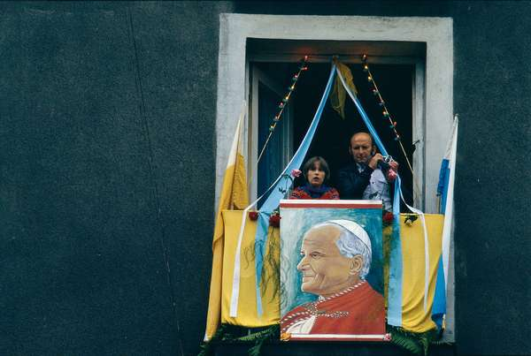Two people are appearing at a window decorated with a portrait of the pope, on the occasion of Pope John Paul II to Poland