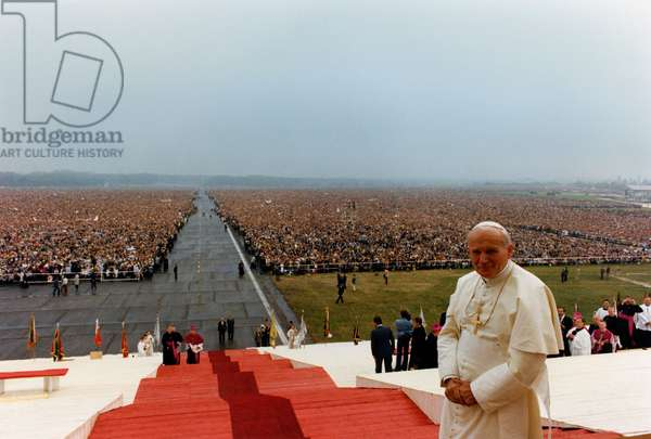 Pope John Paul II and a crowd of Christian believers waiting for him