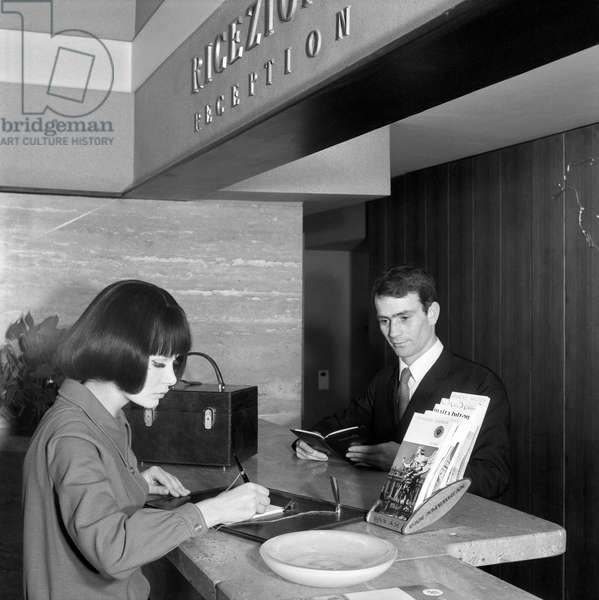 A woman signing a paper at the hotel reception, Italy