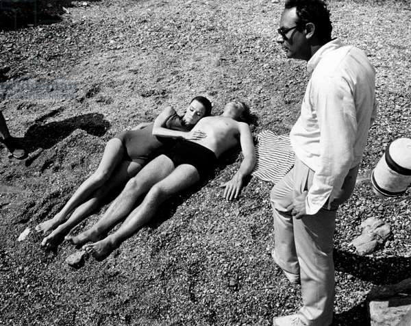 Director Stanley Donen beside Audrey Hepburn and Albert Finney, lying on the beach, 1966 (b/w photo)