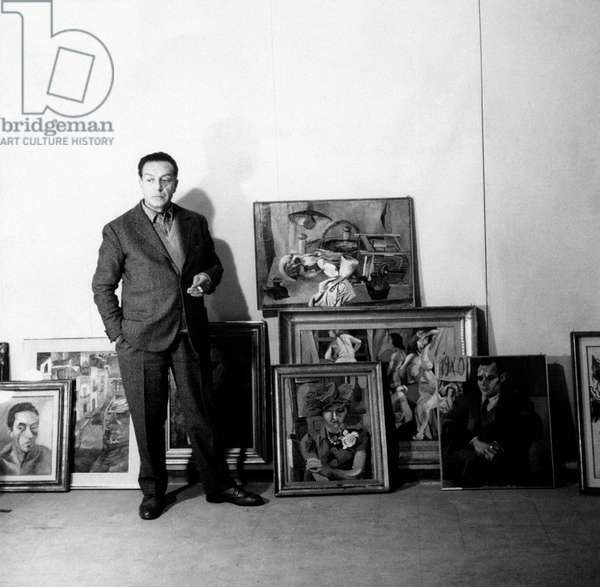 Renato Guttuso poses beside some of his works of art