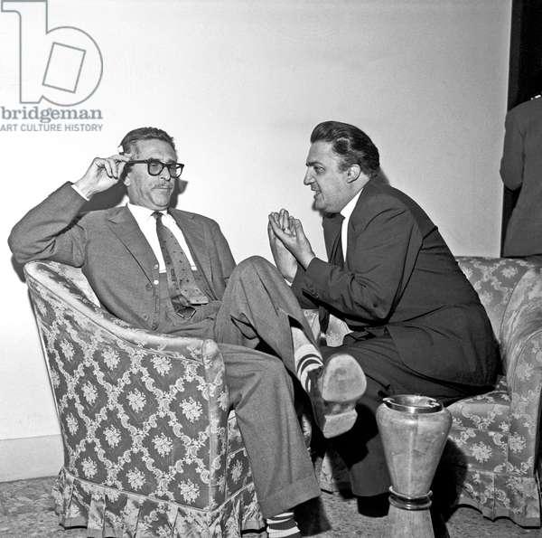 Mario Soldati and Federico Fellini at the cocktail in Cinecittà, Rome, Italy, 1958 (b/w photo)