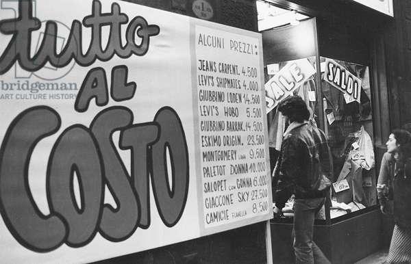 People entering a shop displaying goods on sale, Milan, 1979 (photo)