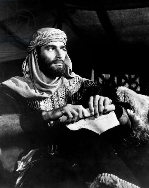 Charlton Heston dressed in costume with a rolled up parchment in his hands