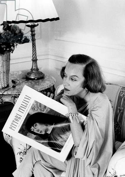 Gloria Swanson leafing through a magazine