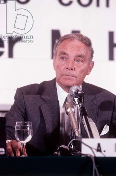 Alexander Haig sitting at a table during a diplomatic meeting