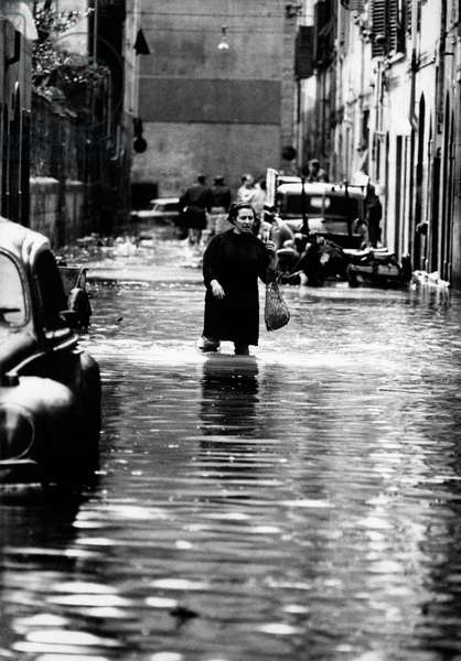 Woman crossing a flooded street