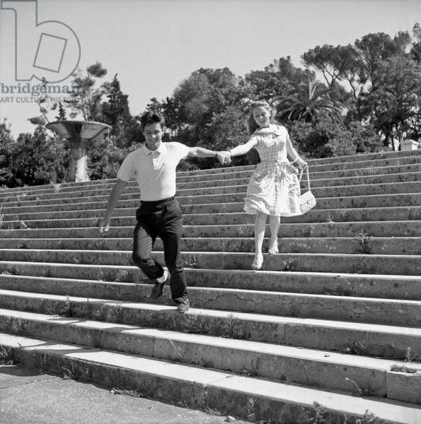 Two young people in love running down steps, Italy 1960s