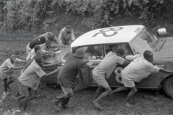 Some people pushing a car bogged down in the mud between Himo and Loitokitok at the border between Kenya and Tanzania during the East African Safari Rally, Africa, April 1965 (b/w photo)