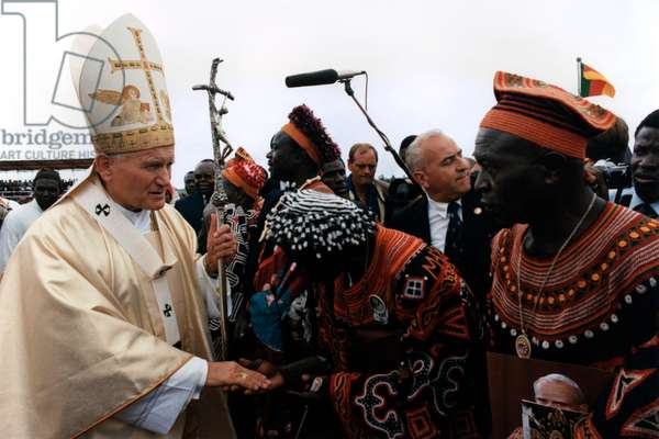 Pope John Paul II greets Christian believers wearing traditional clothing
