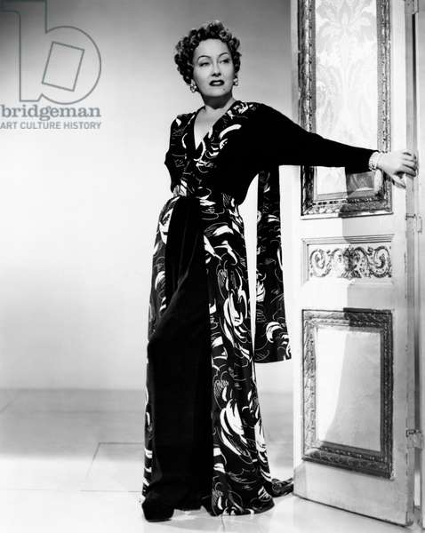 Gloria Swanson with a long dress leant on a door