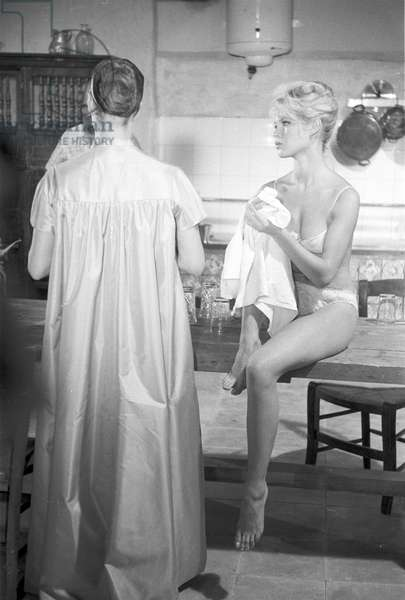 Brigitte Bardot drying her hands sitting on a table on the set, Spain, 1958 (b/w photo)