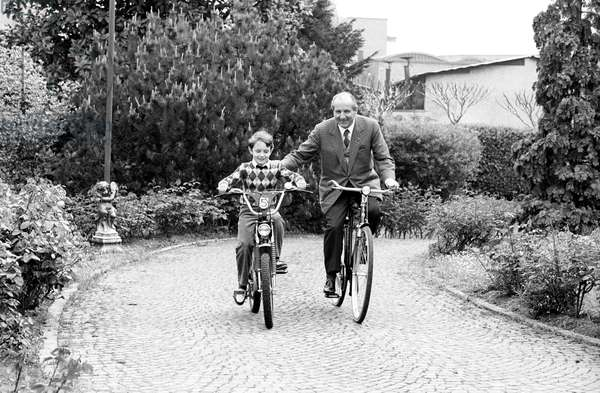 Luigi Lucchini riding a bicycle beside his grandson