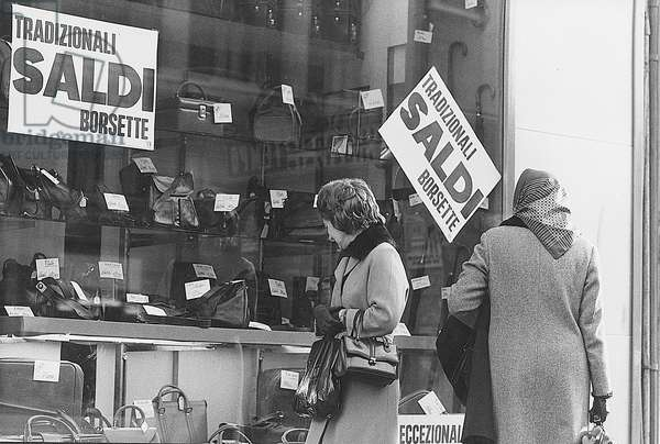 Women watching the window of a leather goods shop displaying goods on sale, Milan, January 1973 (photo)