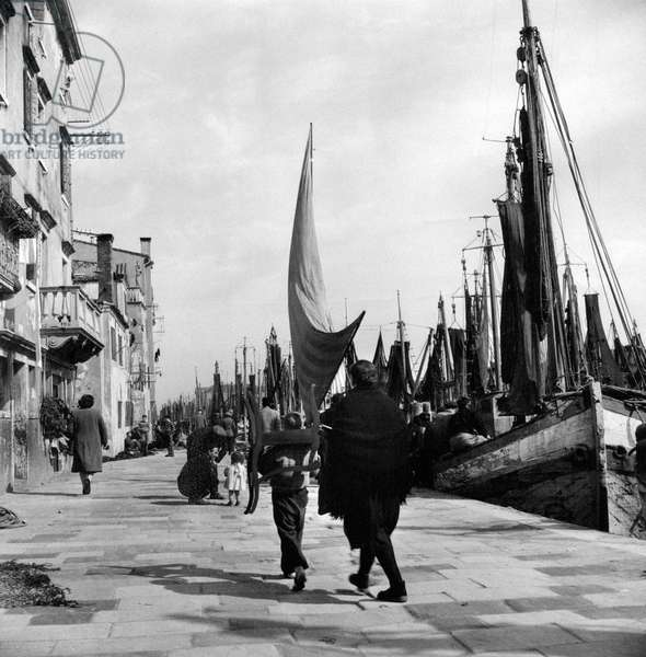 A boy carrying a chair along the pier of Chioggia, at which some fishermens' boats are docked, Chioggia, Italy, March 1954 (b/w photo)
