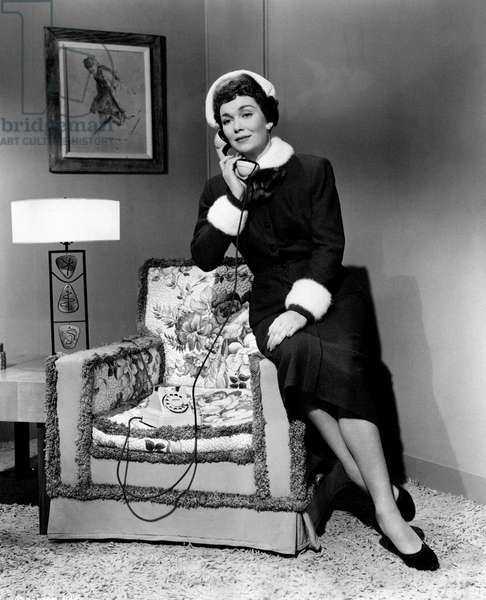 Jane Wyman at the phone seated on the arm of an armchair