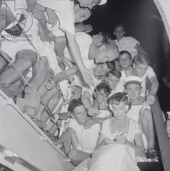 An actress signing autographs to the sailors, Italy, 1955 (b/w photo)