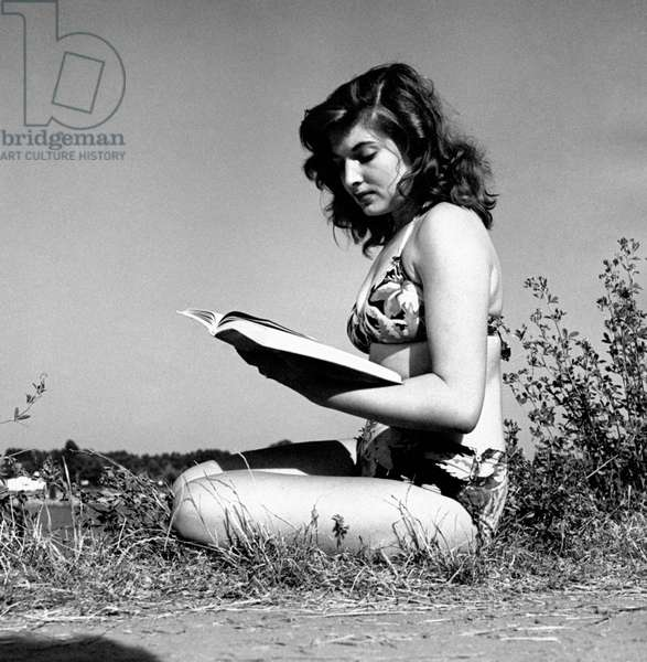 A girl reads a book sitting on the grass, Italy, 1955 (b/w photo)