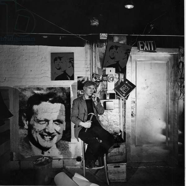 Portrait of Andy Warhol posing with a phone in his workshop The Factory in NY, 1966 (b/w photo)