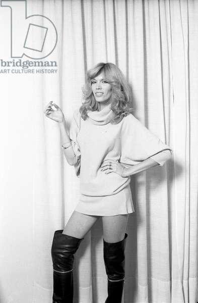 Amanda Lear wearing a miniskirt and boots