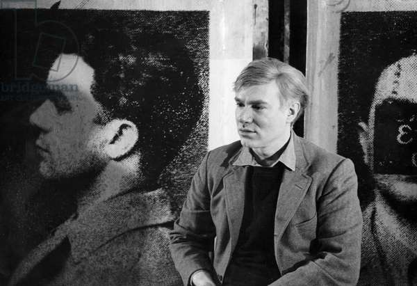 Portrait of andy warhol next to one of his serigraphies in his workshop The Factory, 1966 (b/w photo)