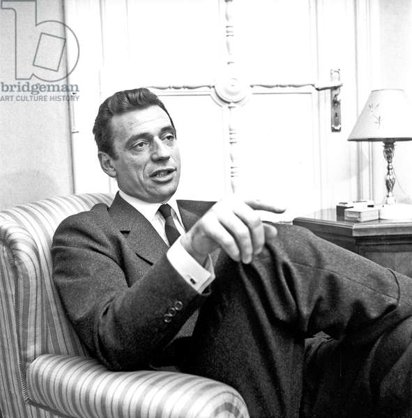 Yves Montand sitting in an armchair, , 1958 (b/w photo)