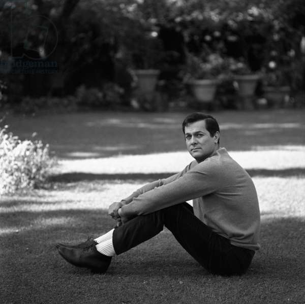 Tony Curtis sitting in the garden of his villa, Rome, Italy