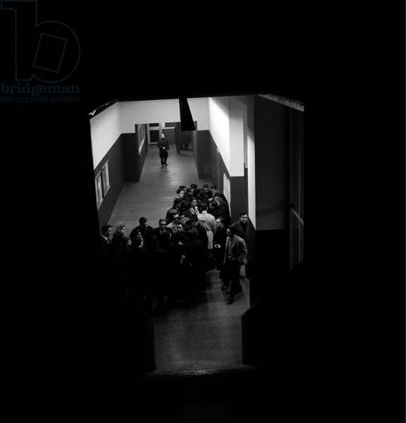 Students discussing along the corridor of a university, Italy