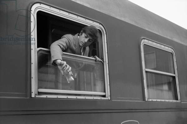 A man leaning out of a train window, Italy