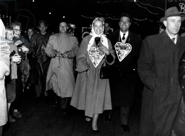 Raf Vallone and Maria Schell strolling among the people, 1956 (b/w photo)