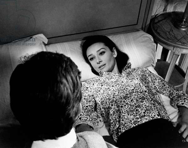Audrey Hepburn lying on the bed, talks with Albert Finney, sitting beside her, 1966 (b/w photo)