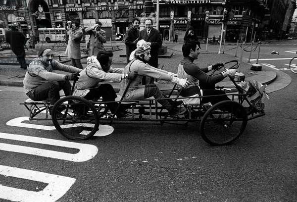 Men crossing Piazza del Duomo on a tandem bicycle in Milan,  Milan, Italy