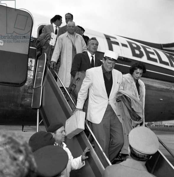 John Wayne, Rossano Brazzi and Sophia Loren arriving at Ciampino airport, Italy, 1957 (b/w photo)