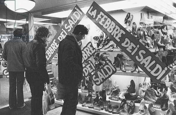 Men watching the window of a shoe shop displaying goods on sale, Milan, 1979 (photo)