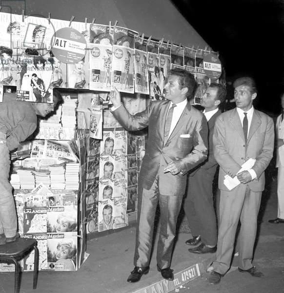 Liberace beside a newsstand in Rome, Rome, Italy, 1959 (b/w photo)