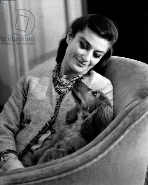 Anouk Aimée sitting in an armchair with her female dog Lulù, 1963 (b/w photo)