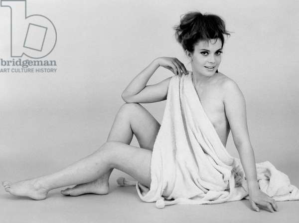 Stefania Careddu is smiling while seated on the floor; she is wearing only a large towel, 1972 (b/w photo)
