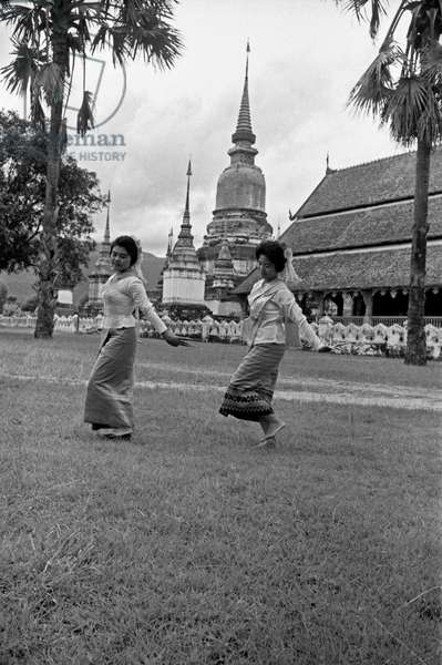Two Thai girls dancing in the garden of a Buddhist temple, Bangkok, 1961 (b/w photo)