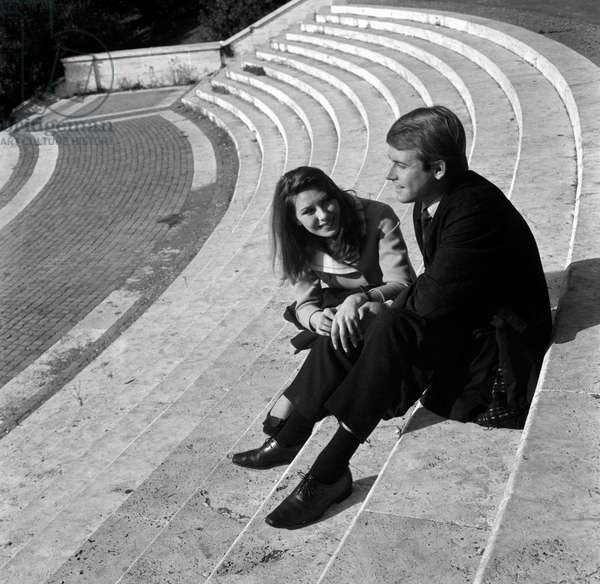 Two young people chatting seated on a staircase, Italy