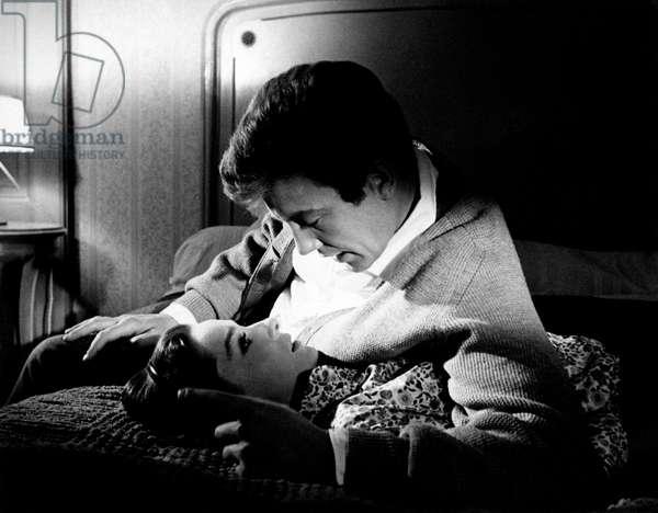 Audrey Hepburn and Albert Finney, lying in bed, shoot a romantic scene, 1966 (b/w photo)