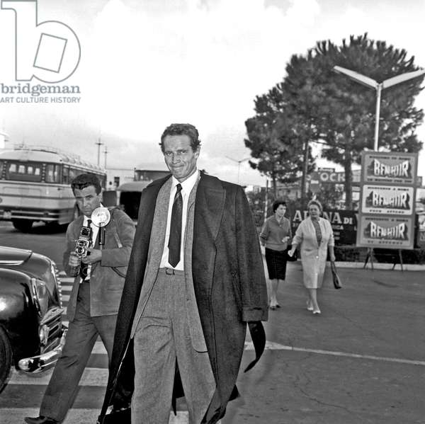 Charlton Heston arriving at Ciampino airport, Rome, Italy, 1960 (b/w photo)