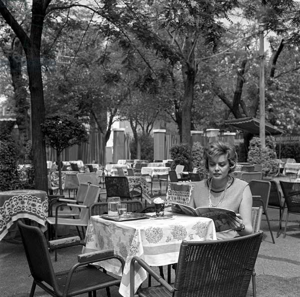 A lonely woman sitting at the table of an outdoor café, Italy