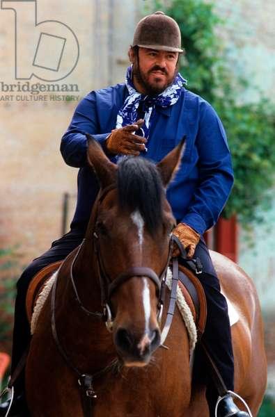 Luciano Pavarotti on a horse saddle