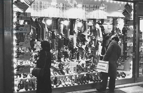 People watching the window of a shop displaying goods on sale, Milan, 1979 (photo)